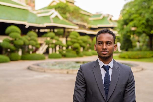 Retrato de jovem empresário africano bonito pensando ao ar livre