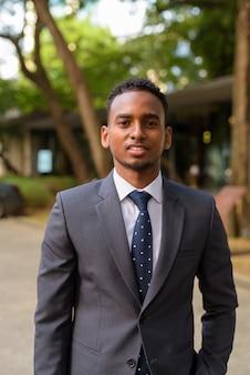 Retrato de jovem empresário africano bonito sorrindo ao ar livre