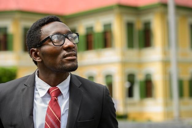 Retrato de jovem empresário africano bonito vestindo terno nas ruas da cidade ao ar livre