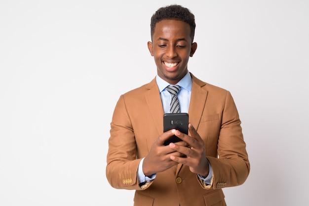 Retrato de jovem empresário africano com cabelo afro em um terno marrom contra uma parede branca