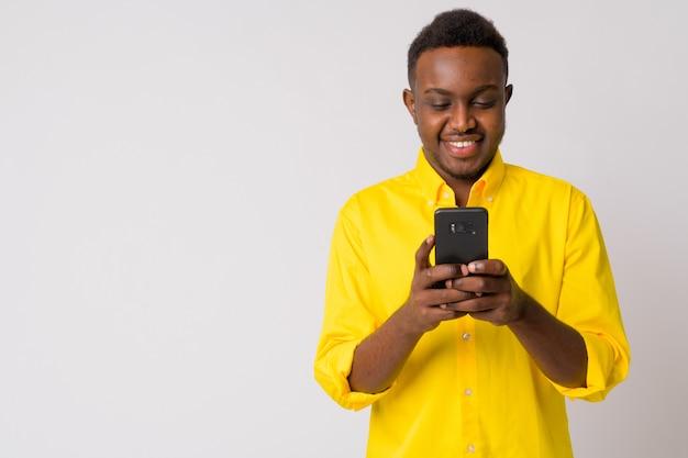 Retrato de jovem empresário africano com camisa amarela contra uma parede branca