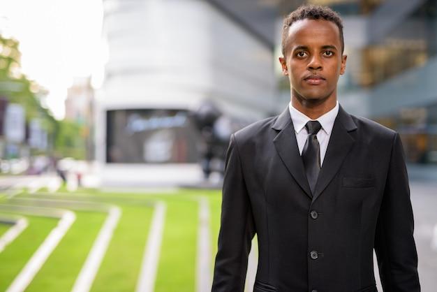 Retrato de jovem empresário africano de sucesso ao ar livre