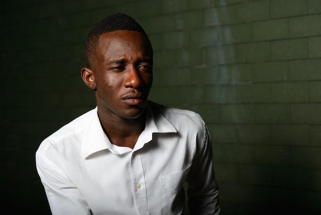 Retrato de jovem empresário africano no escuro contra uma parede de tijolos à noite Foto Premium
