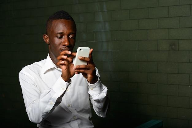 Retrato de jovem empresário africano no escuro contra uma parede de tijolos à noite