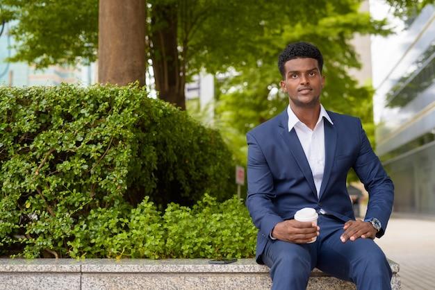 Retrato de jovem empresário africano segurando uma xícara de café para levar ao ar livre na cidade enquanto está sentado, tiro horizontal