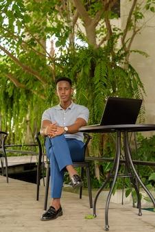 Retrato de jovem empresário africano vestindo roupas casuais e sentado em uma cafeteria enquanto usa o computador laptop e o distanciamento social