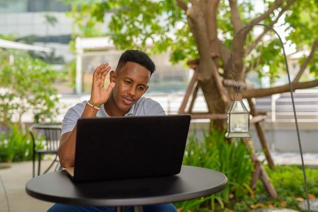 Retrato de jovem empresário africano vestindo roupas casuais e sentado em uma cafeteria