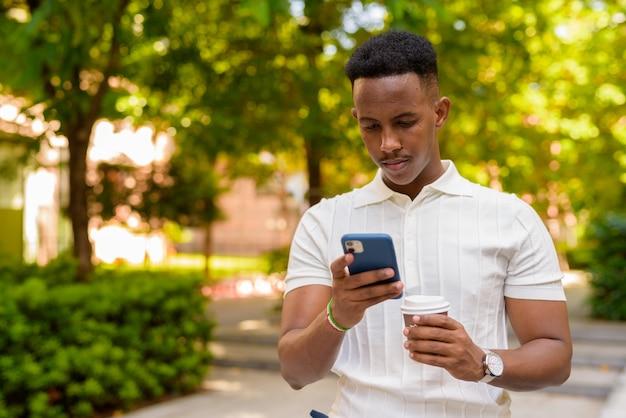 Retrato de jovem empresário africano vestindo roupas casuais e usando telefone celular segurando uma xícara de café no parque