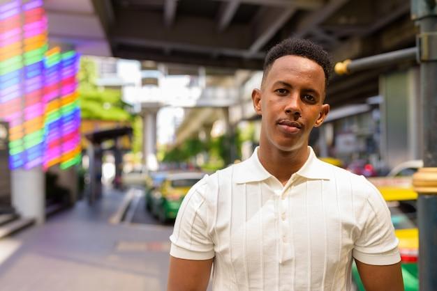Retrato de jovem empresário africano vestindo roupas casuais enquanto espera um táxi
