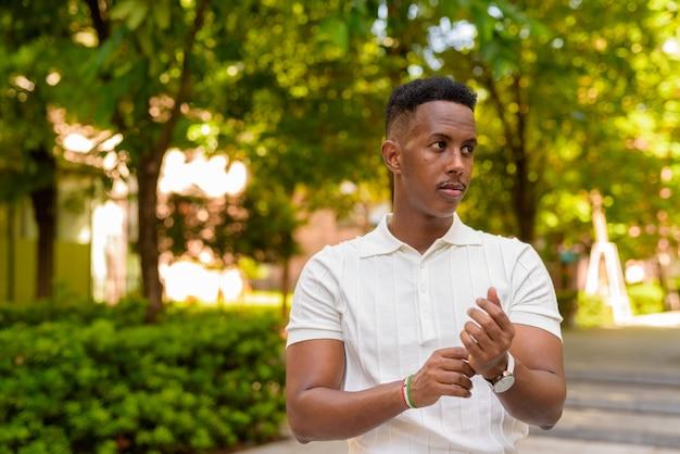 Retrato de jovem empresário africano vestindo roupas casuais no parque enquanto pensa