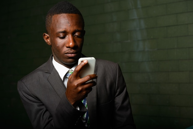 Retrato de jovem empresário africano vestindo terno contra uma parede de tijolos no escuro Foto Premium