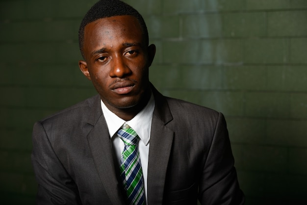 Retrato de jovem empresário africano vestindo terno contra uma parede de tijolos no escuro