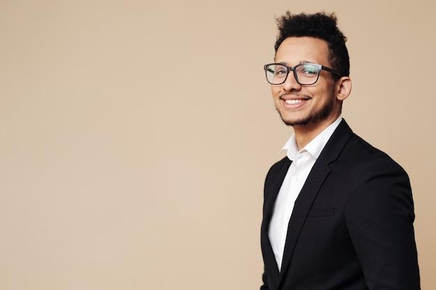 Retrato de jovem empresário afro, vestindo camiseta, terno preto, óculos e olhando para a frente em pé na parede bege