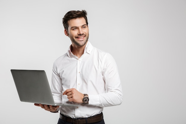 Retrato de jovem empresário alegre em um relógio de pulso segurando e usando laptop isolado no branco