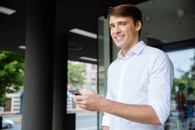 Retrato de jovem empresário alegre usando smartphone e sorrindo perto do centro de negócios