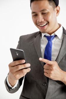 Retrato de jovem empresário animado segurando uma parede branca com telefone isolado