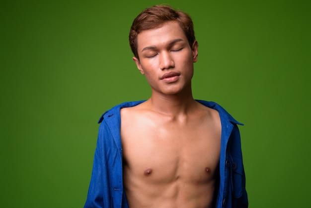 Retrato de jovem empresário asiático contra parede verde