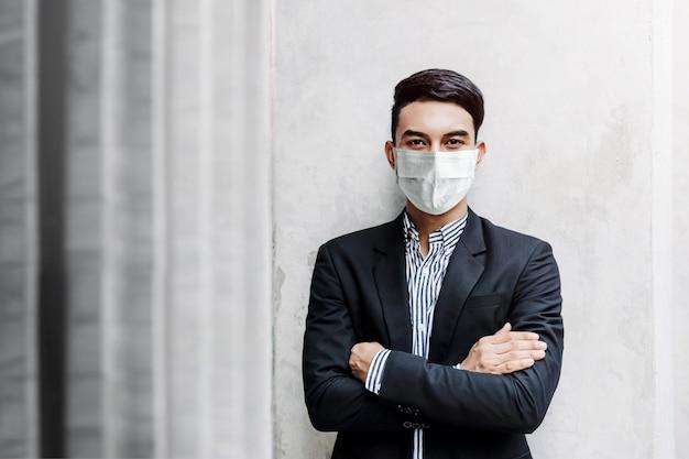 Retrato de jovem empresário asiático usando máscara cirúrgica e em pé na parede