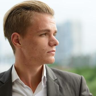 Retrato de jovem empresário bonito com cabelo loiro e terno contra a vista da cidade