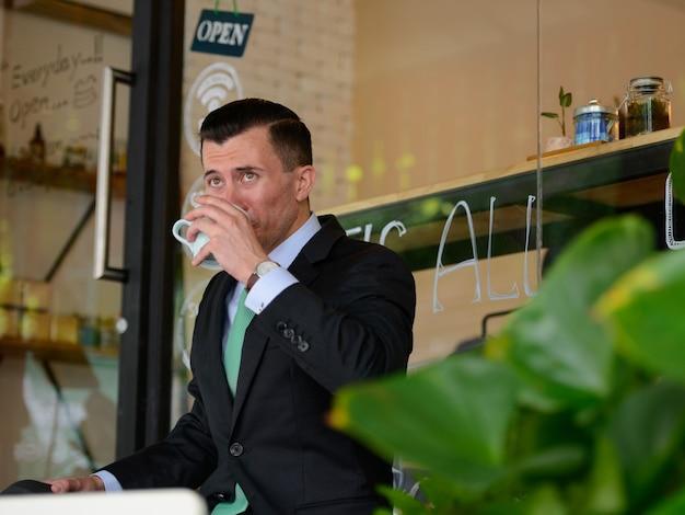 Retrato de jovem empresário bonito de terno no café ao ar livre