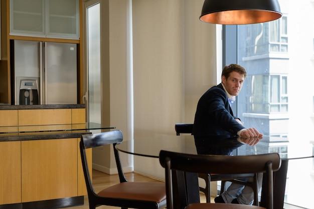 Retrato de jovem empresário bonito sentado na sala de jantar perto da cozinha