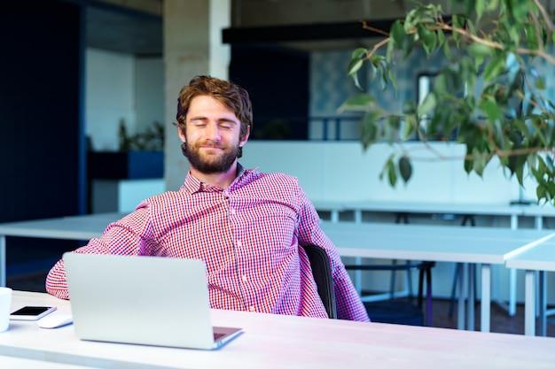 Retrato de jovem empresário caucasiano usando laptop em seu local de trabalho em um escritório moderno