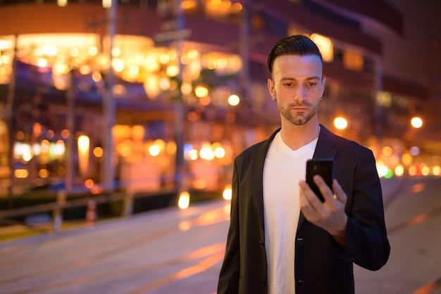 Retrato de jovem empresário contra uma cidade à noite