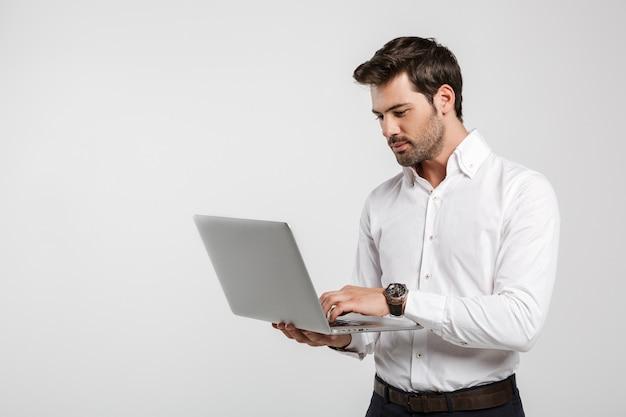 Retrato de jovem empresário de sucesso em um relógio de pulso segurando e usando laptop isolado no branco
