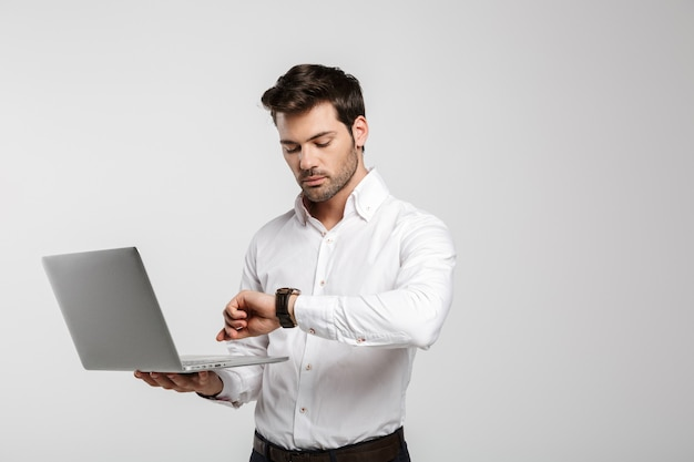 Retrato de jovem empresário de sucesso segurando laptop e olhando para um relógio de pulso isolado no branco