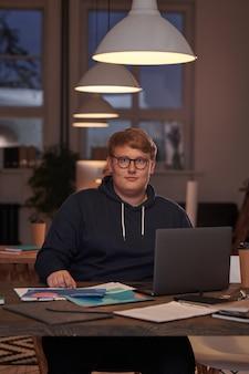Retrato de jovem empresário em óculos, olhando para frente enquanto trabalhava na mesa com o laptop no escritório