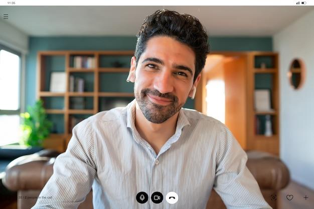 Retrato de jovem empresário em uma videochamada de trabalho enquanto fica em casa