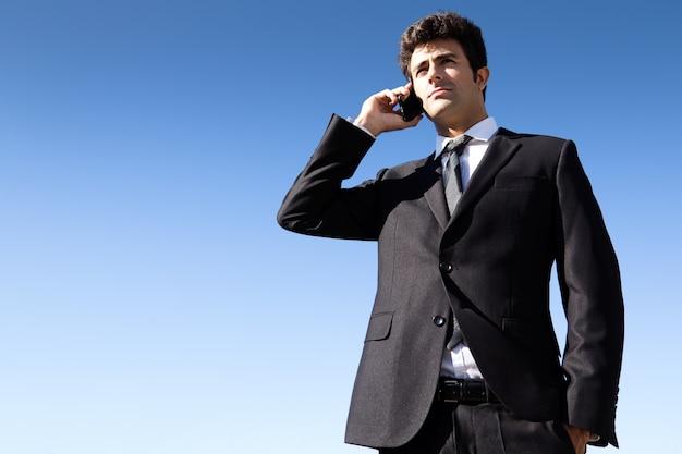 Retrato de jovem empresário falando com smartphone