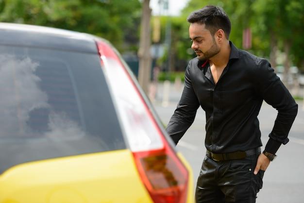 Retrato de jovem empresário indiano barbudo bonito na cidade ao ar livre