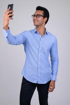 Retrato de jovem empresário indiano bonito em branco