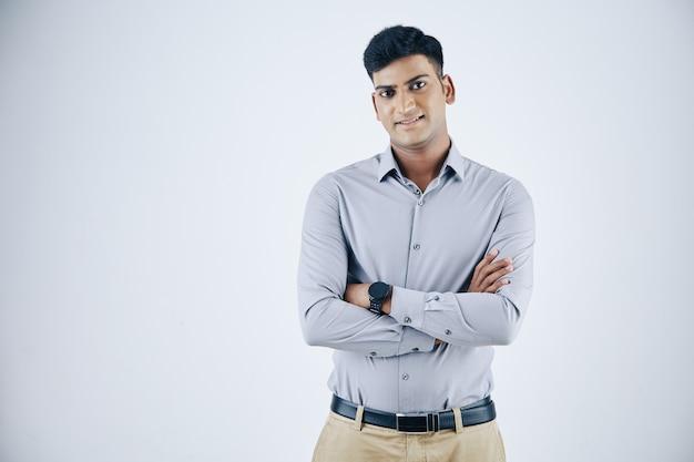 Retrato de jovem empresário indiano, cruzando os braços e sorrindo para a câmera