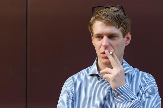 Retrato de jovem empresário loiro bonito nas ruas da cidade ao ar livre