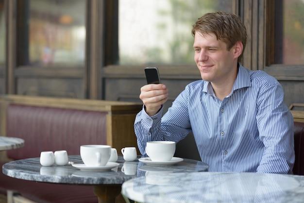 Retrato de jovem empresário loiro bonito relaxando em uma cafeteria ao ar livre