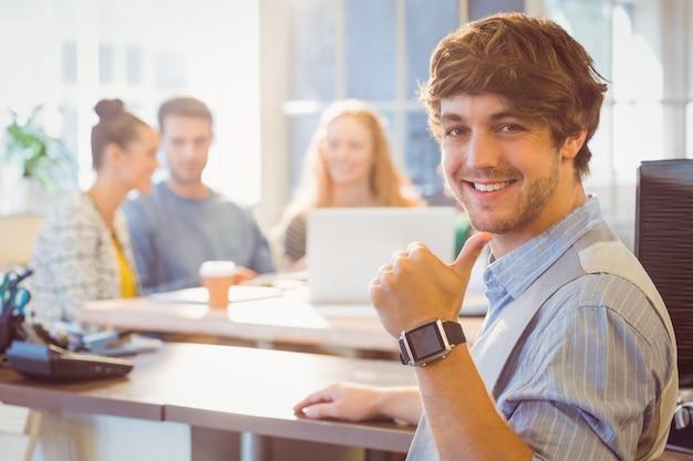 Retrato de jovem empresário sorridente com colegas