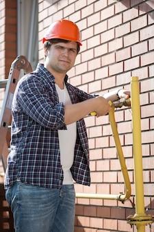Retrato de jovem encanador com capacete de segurança fazendo manutenção de canos de gás amarelos fora de casa