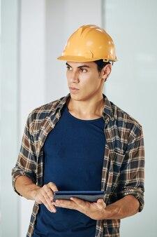 Retrato de jovem engenheiro civil sério com tablet digital nas mãos, olhando para longe