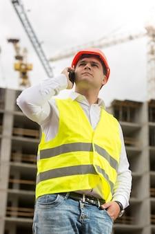 Retrato de jovem engenheiro de construção falando por telefone no canteiro de obras
