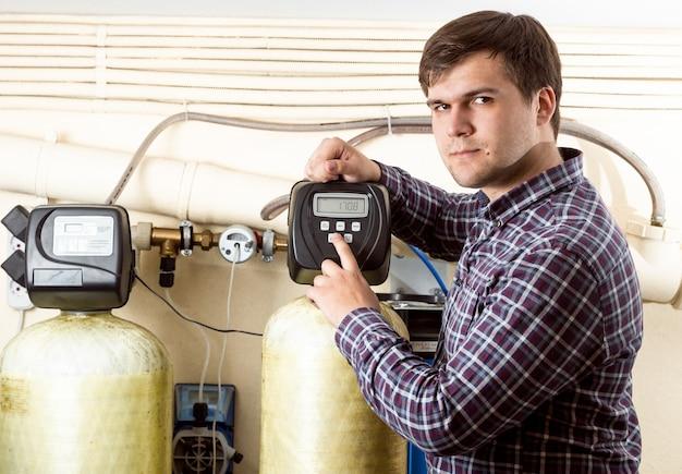 Retrato de jovem engenheiro pressionando o botão no painel de controle com tela monocromática