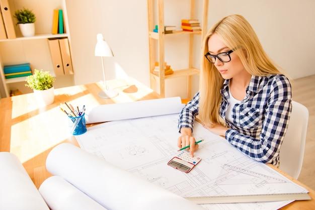 Retrato de jovem engenheiro usando calculadora para finalizar o projeto