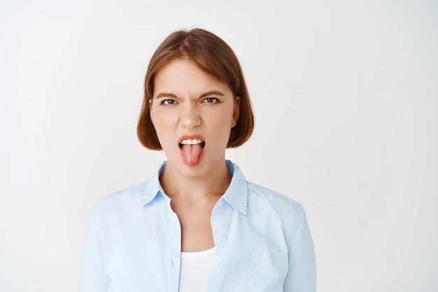 Retrato de jovem enojado, mostrando a língua e carrancudo, odeio algo, opinião negativa. menina não gosta de algo de mau gosto, encostada em uma parede branca