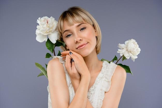 Retrato de jovem entre flores ao longo da parede cinza