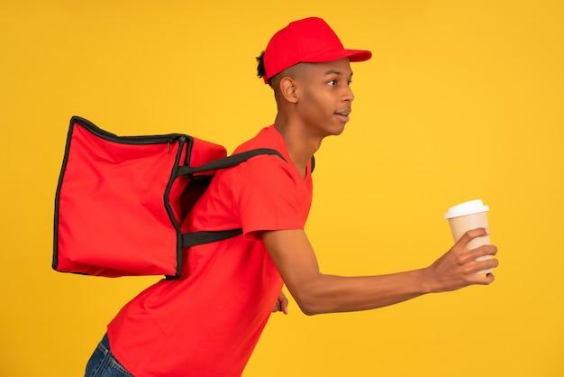 Retrato de jovem entregador de uniforme vermelho, correndo com um café para viagem. conceito de serviço de entrega.