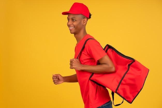 Retrato de jovem entregador vestido com um uniforme vermelho atropelando fundo isolado. conceito de entrega.
