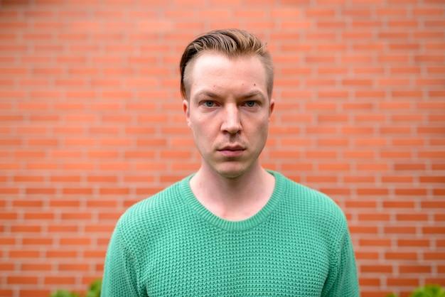 Retrato de jovem escandinavo bonito com cabelo loiro contra uma parede de tijolos
