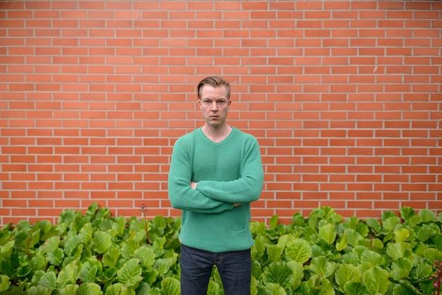 Retrato de jovem escandinavo bonito com cabelo loiro contra uma parede de tijolos Foto Premium
