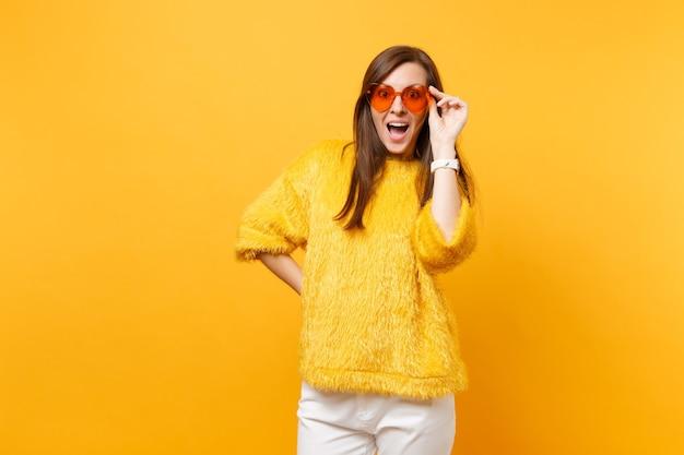 Retrato de jovem espantado animado em suéter de pele, calça branca segurando coração laranja óculos isolados no fundo amarelo brilhante. emoções sinceras de pessoas, conceito de estilo de vida. área de publicidade.